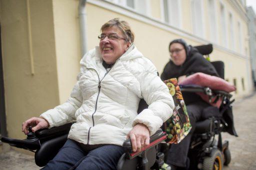 Draußen: Zwei lachende Menschen im Rollstuhl.