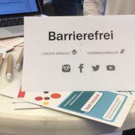 """Tisch mit verschiedenen Materialien und einem Aussteller aus Papier. Darauf die Stichworte """"Barrierefrei"""" """"Leichte Sprache"""" und """"Gebärdensprache"""" sowie die Symbole für Instagram, Facebook, Twitter und YouTube."""