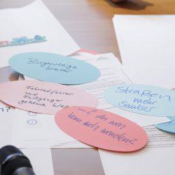 Mehrere bunte ovalförmige Moderationskarten mit Notizen auf einem Tisch.