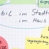 """Ausschnitt eines Flipcharts mit bunten beschrifteten Kärtchen. In der Mitte steht """"Mobil im Stadtteil"""" und """"im Haus"""". Darum: """"Welche Hindernisse?"""" """"Was brauchen wir?"""" und der Stichpunkt """"Wegebegleitung"""""""