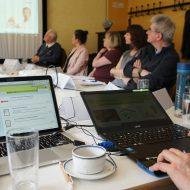 Mehrere Personen sitzen an einem Tisch und schauen auf eine präsentation der Deutschen Gebärdensprache. Im Vordergrund sitzt eine Person, die den Computer bedient.