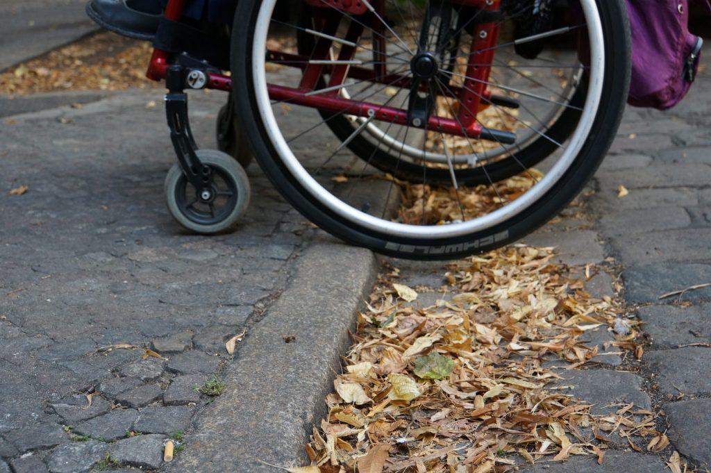 Ein Rollstuhl in Großaufnahme an einer Bordsteinkante