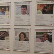 Wand mit verschiedenen Postern, auf denen Menschen mit Foto und Text portraitiert werden