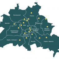 dunkelgrüne Berlin-Karte mit 20 gelben Häusern hervorgehoben