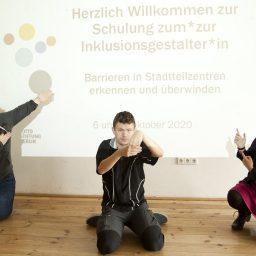 Drei DozentInnen sitzend oder kniend vor dem Beamerbild, welches die Begrüßungsfolie zur Schulung zeigt: links Christine Pargmann, in der Mitte Patrick Marx und rechts Stefanie Wiens.